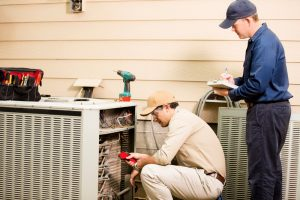 two technicians working on the outdoor unit of an air conditioning system
