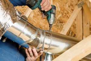technicians hands drilling ductwork together