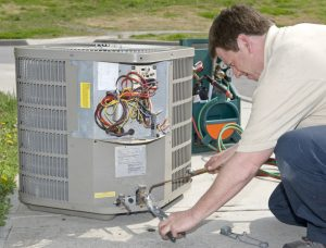 An air conditioning technician welds a connection prior to installing AC unit.