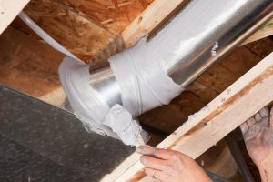 A dirty male hand, holding a paintbrush, is spreading caulk over a house air duct joint with a paintbrush. The caulk has been applied from a tube with a caulk gun and the brush is evenly spreading it over the joint. Caulking residential ducts prevents air-conditioned or heated air from escaping the duct and prevents ambient air from entering the system. This is a new practice in homebuilding to increase energy efficiency, eventually it may be come standard or mandatory.